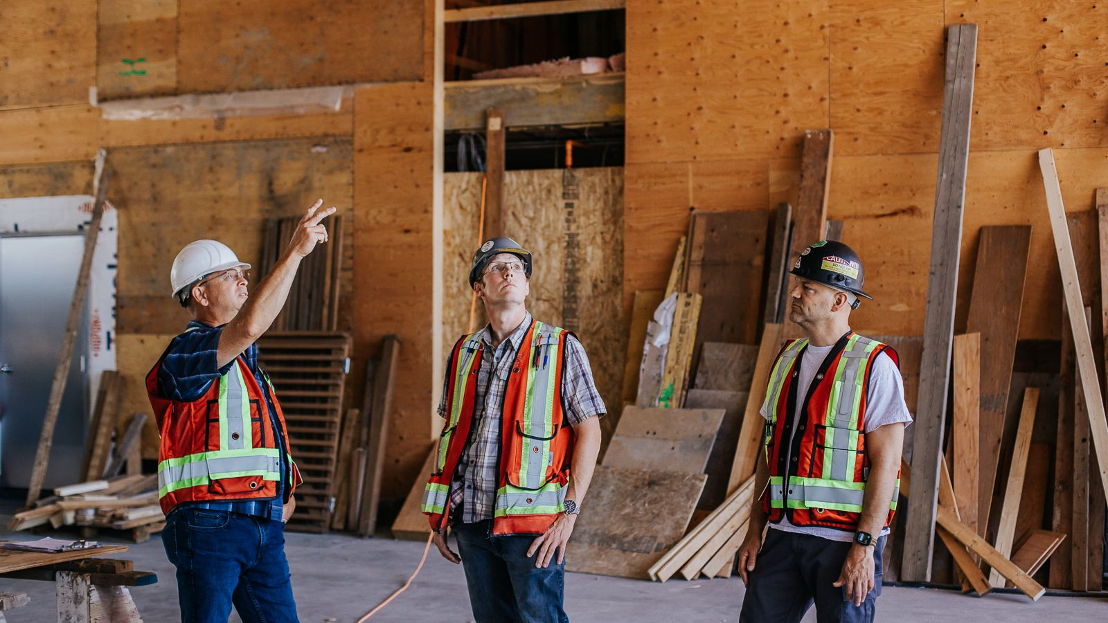 Three Kelco Drywall employees in safety hats and vests as they inspect a drywall installation job by Kelco Drywall.