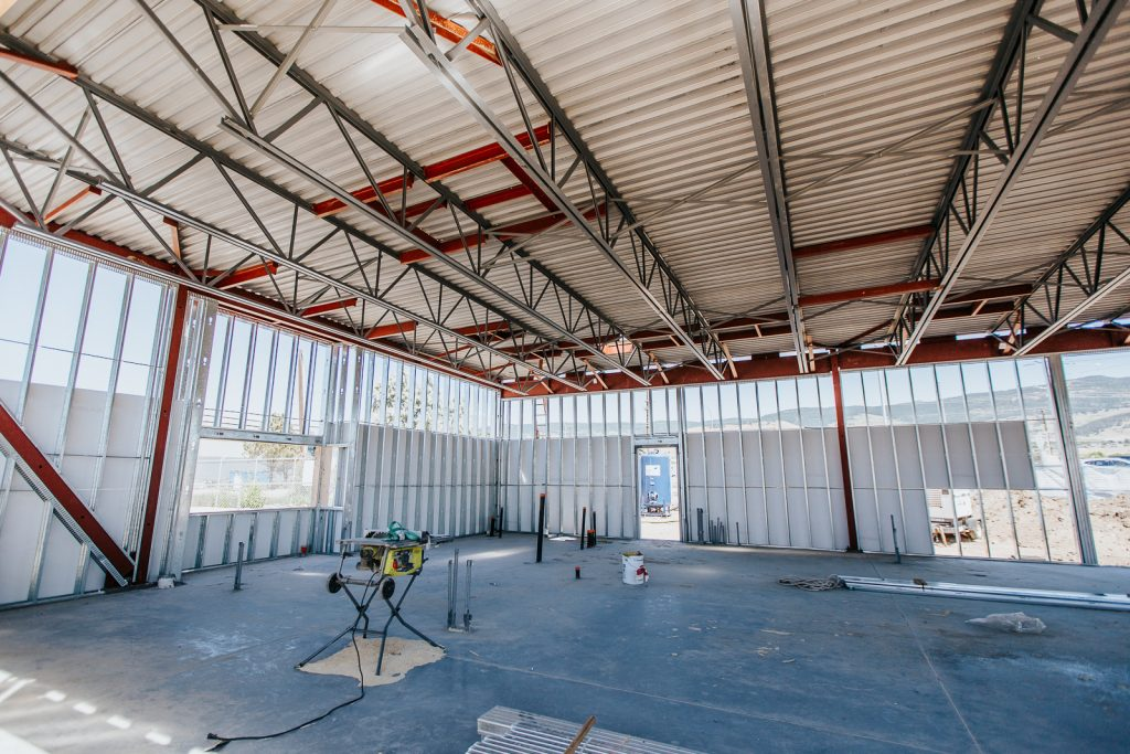 An example of Kelco Drywall's steel stud framing work, in a large room with steel frames and concrete floors.