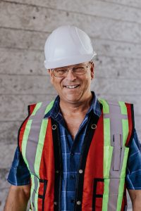 Profile picture of one of the Kelco Drywall employees, he is wearing a helmet as well as a safety vest.