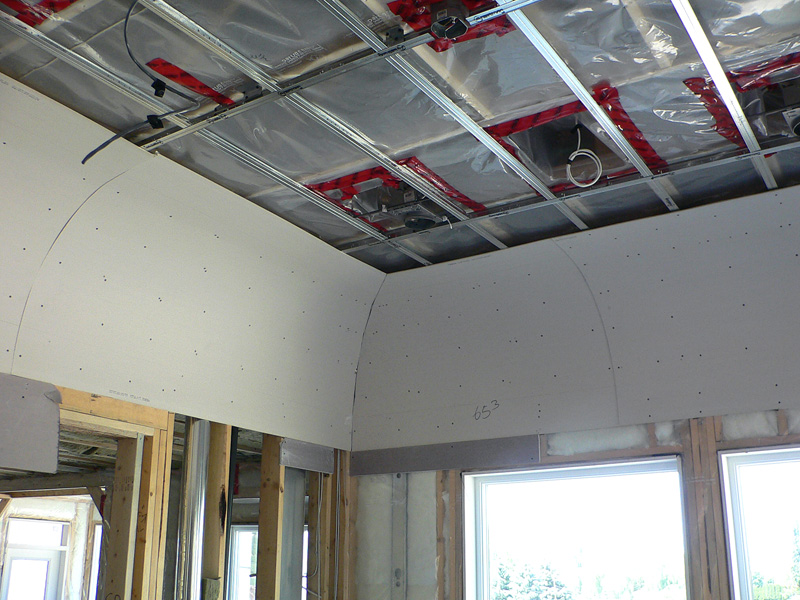A room with specialty framing by Kelco drywall, which is framed with metal framework and plastic sheets, along with curved wooden sheets.