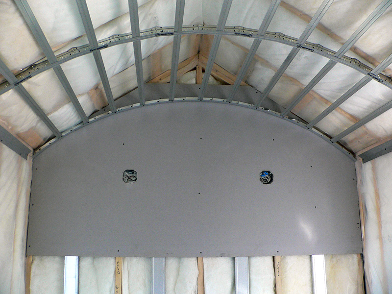 A room with metal frames midway through a specialty framing installation by Kelco Drywall in a curved-ceiling room.