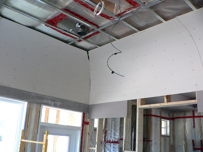 An example of Kelco drywall's specialty framing mid way through installation, which shows metal frames and wooden curved sheets