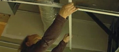 A Kelco Drywall crew member installing steel stud framing to a ceiling for an acoustical ceiling system.